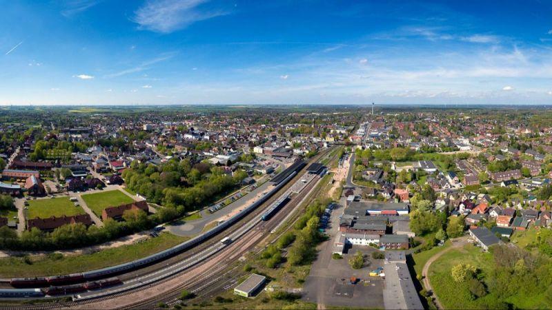 """Das Luftbild zeigt das Quartier """"Rüsdorfer Kamp"""" in Heide aus der Vogelperspektive. Das Quartier befindet sich im Bereich rechts neben den Gleisen."""