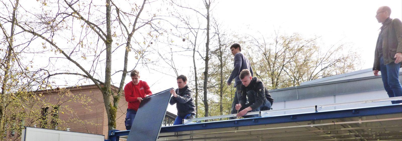 Studierende und Auszubildende installieren die photovoltaisch-thermische (PVT) Hybridanlage auf dem Containerdach.