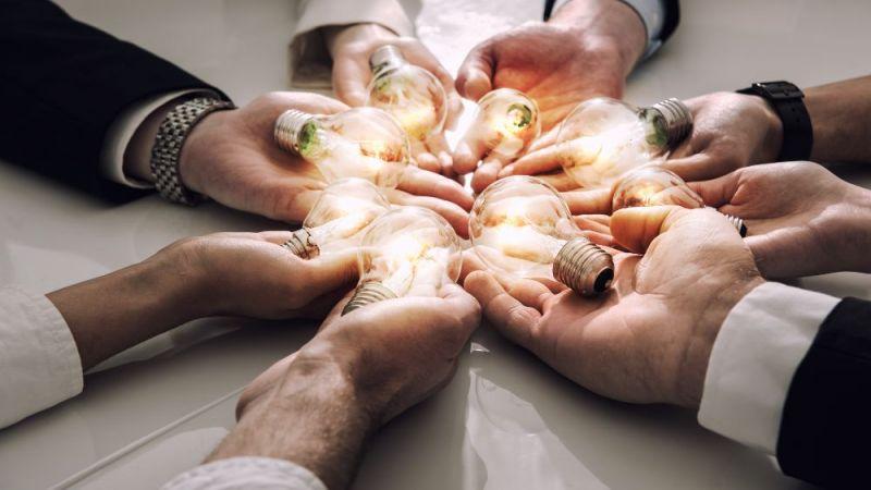 Hände halten Glühbirnen in die Mitte eines Kreises