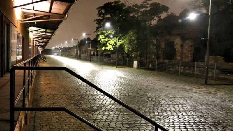 Mit LED Wege und Plätze effizient beleuchten: Zu sehen ist ein Abschnitt der Ladestraße, die mit Masten bestückt ist, die jeweils in unterschiedlicher Höhe mit drei Leuchten ausgestattet sind.