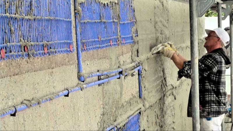 Die Kapillarrohrmatten werden als Flächenheizsystem außen auf die Fassade aufgebracht. Im Bild wird gerade der Klebemörtel glatt gezogen für den Leichtputz.