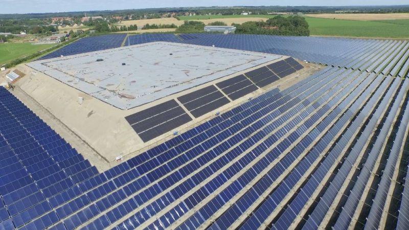 Hier sieht man einen Erdbeckenwärmespeicher mitten in einem Solarthermiefeld im dänischen Gram.