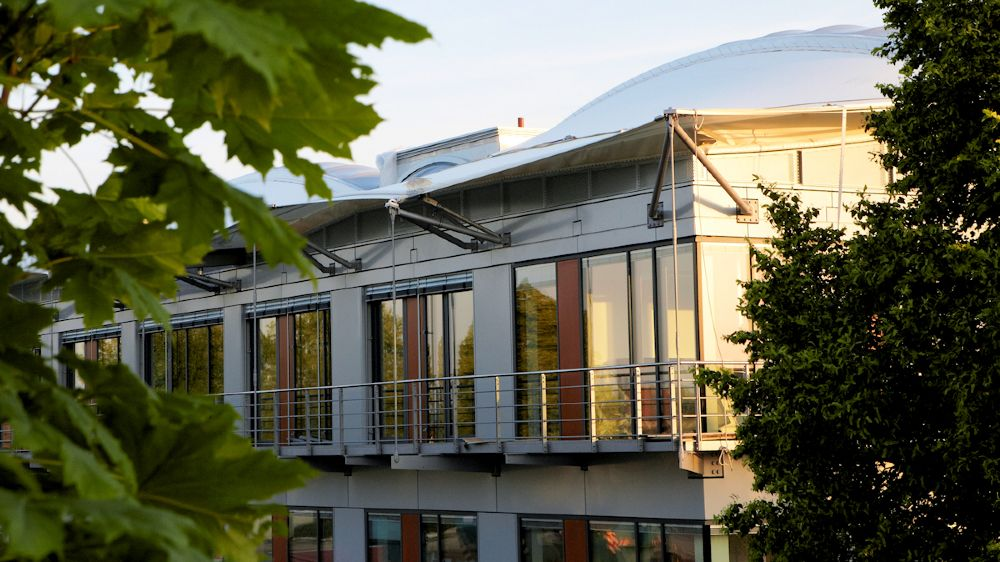 Am auffälligsten ist das textile Dach des Neubaus. Neuartige Membranfolien lassen in Verbindung mit speziellen Deckenelementen Tageslicht in das Gebäude und schaffen zugleich eine regulierbare Zwischenklimazone.