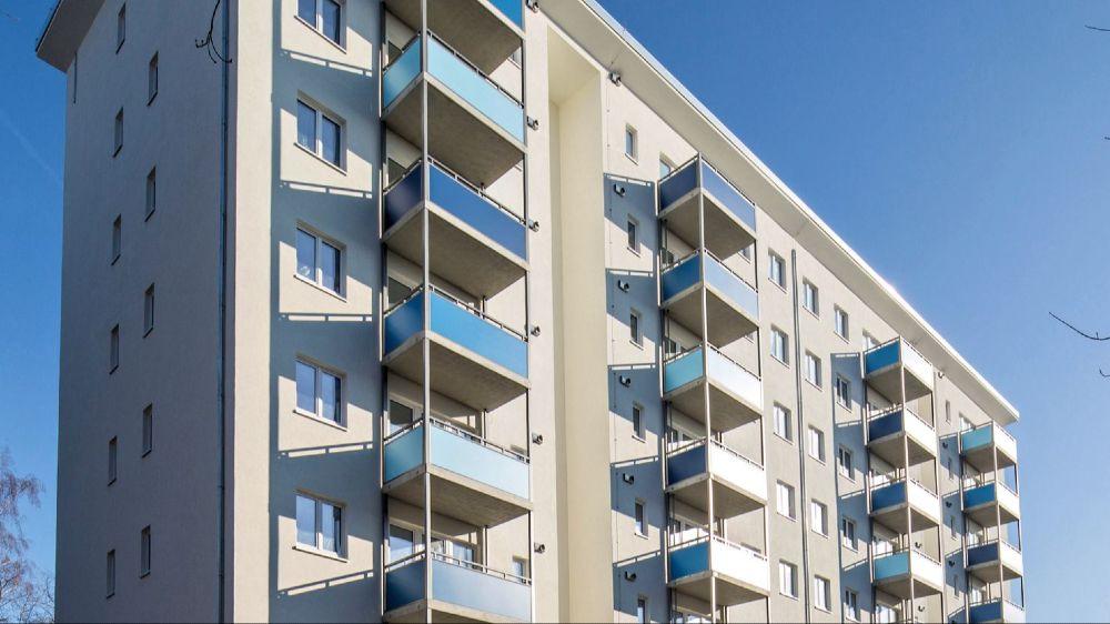 Das 8-geschossige Gebäude aus den 1950er Jahren zeigt sich nach der Sanierung erst einmal unauffällig mit optimiertem Wärmeschutz und vorgesetzten Balkonen.
