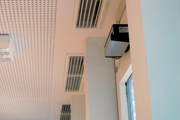 Forschungsfokus  Im Fokus des Teilprojektes stand die Untersuchung von passiven und aktiven Lüftungssystemen mit PCM zur Raumkühlung. Anhand von Messdaten wurden belastbare Systemkennwerte ermittelt und das energetische Potenzial solcher Systeme untersucht.  Im Rahmen des Projektes wurden neben einer hinterlüfteten Kühldecke mit PCM in einem Besprechungsraum auch PCM-Lüftungskompaktspeichergeräte und PCM-Brüstungsmodule in Büroräumen untersucht. Die hinterlüftete Kühldecke mit PCM wurde bereits im Rahmen eines Vorgängerprojektes installiert. Hierbei konnten Kühlleistungen von 15-30 W/m² bei Raumtemperaturen von 26-28°C ermittelt werden. Jetzt sollte die Regeneration des PCM mittels Nachtlüftung optimiert werden.  Deckenlufteinlässe und automatischer Aktor zur Öffnung der Fenster für den Regenerationsbetrieb