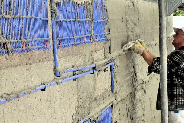 Die Kapillarrohrmatten werden als Flächenheizsystem außen auf die Fassade aufgebracht. Im Bild wird gerade der Klebemörtel glatt gezogen für den Leichtputz. Die außen liegende Wandheizung eignet sich besonders für die Sanierung von Gebäuden.