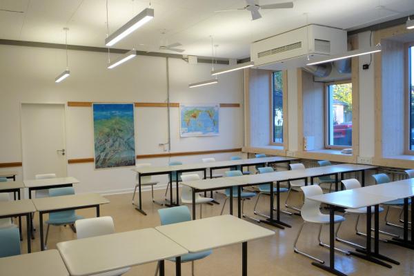 Ein Klassenzimmer. Im Bild die tiefen Fensterlaibungen aufgrund der vorgesetzten Fassade und abgehängte, präsenz- und tageslichtgesteuerte Leuchten. Hier zusätzlich mit Deckenventilatoren, um zu untersuchen, wie diese die Behaglichkeit beeinflussen.